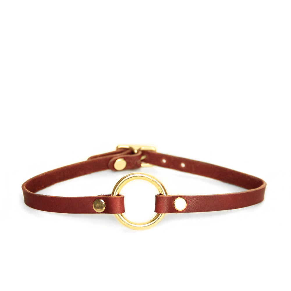 Mini o-ring choker made from a chestnut brown colored leather paired with a brass o-ring and matching hardware.