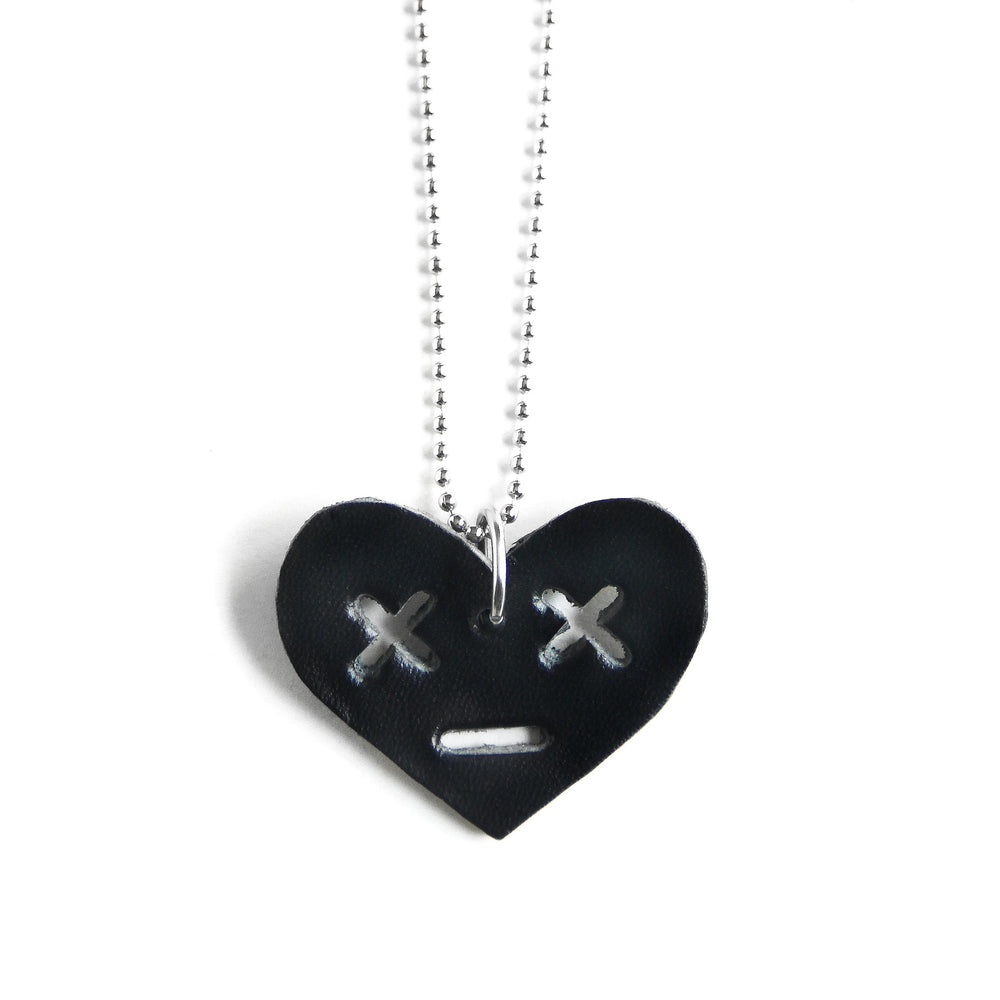 Leather heart necklace with x eyes, close up