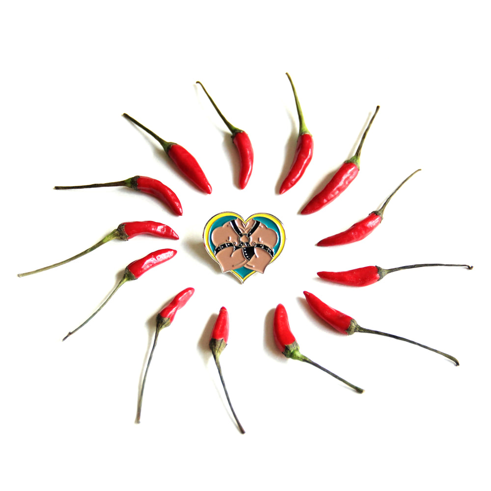 One leather daddy pin lays on a white background with small red peppers arranged in a swirling circle surrounding it.