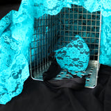 Teal lace face mask in wire cage shown at an angle. Cage is draped with more teal lace fabric.