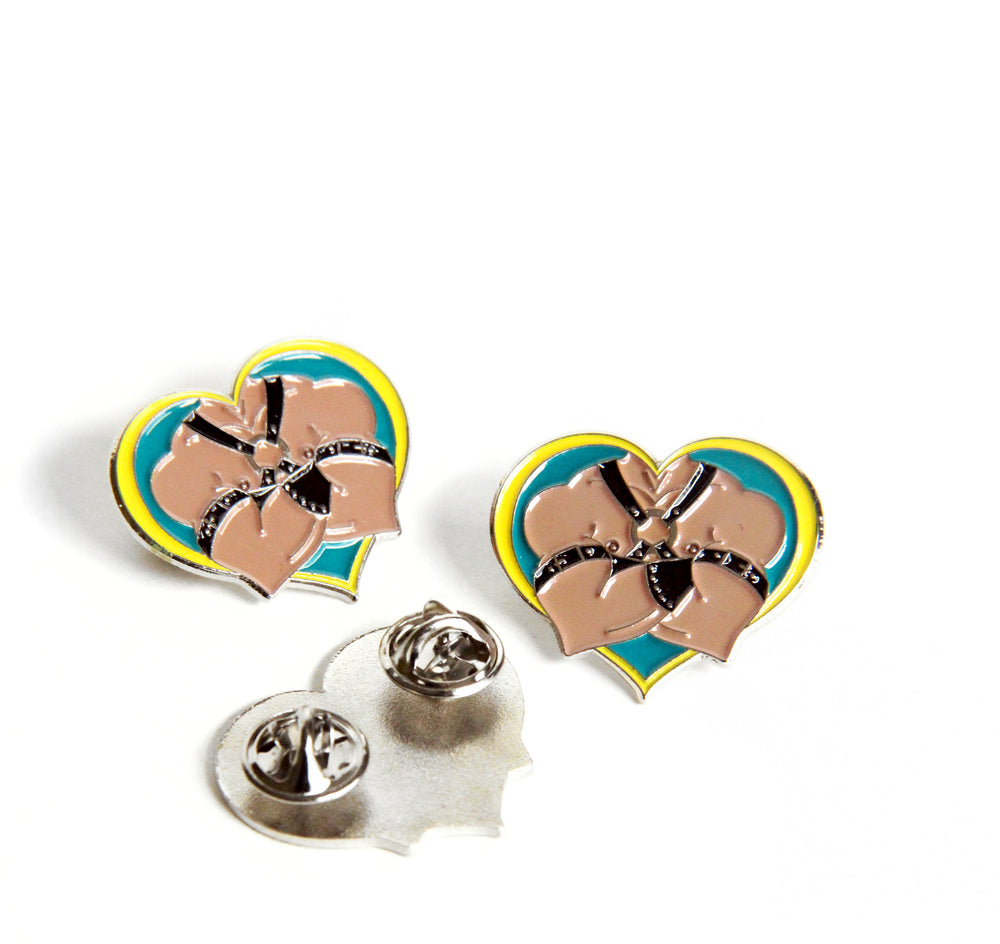 Trio of leather daddy pins on a white background. One is flipped over to show the double butterfly clutch pin backs.