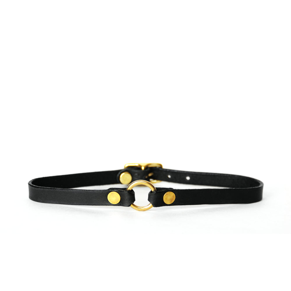 A thin black leather choker with a tiny brass o-ring at center front sits on a white surface with a white background.