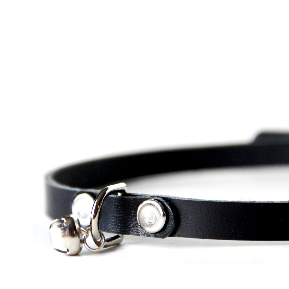 Close up of the mini kitty choker. Shows how d-ring is attached to collar with a small leather strap and jingle bell is attached to d-ring with a small o-ring.