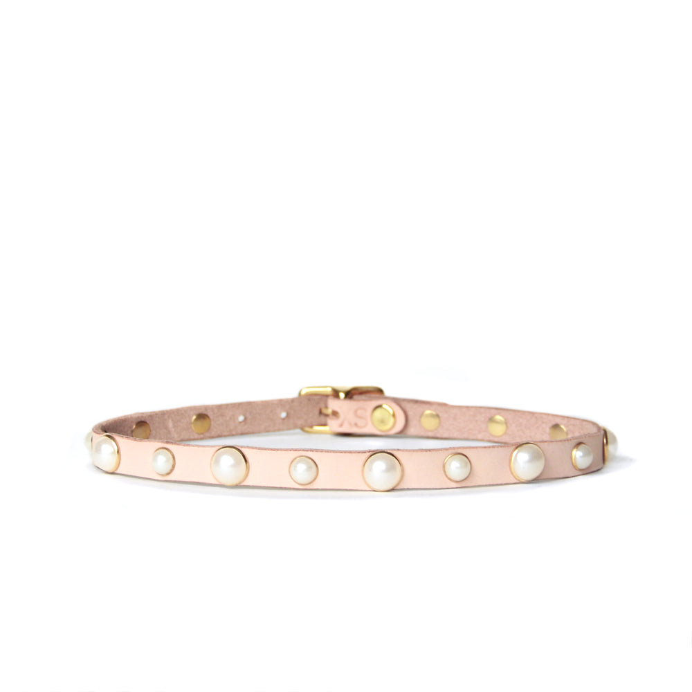 Thin leather choker created from a peachy beige toned natural leather studded with pearls trimmed in gold.