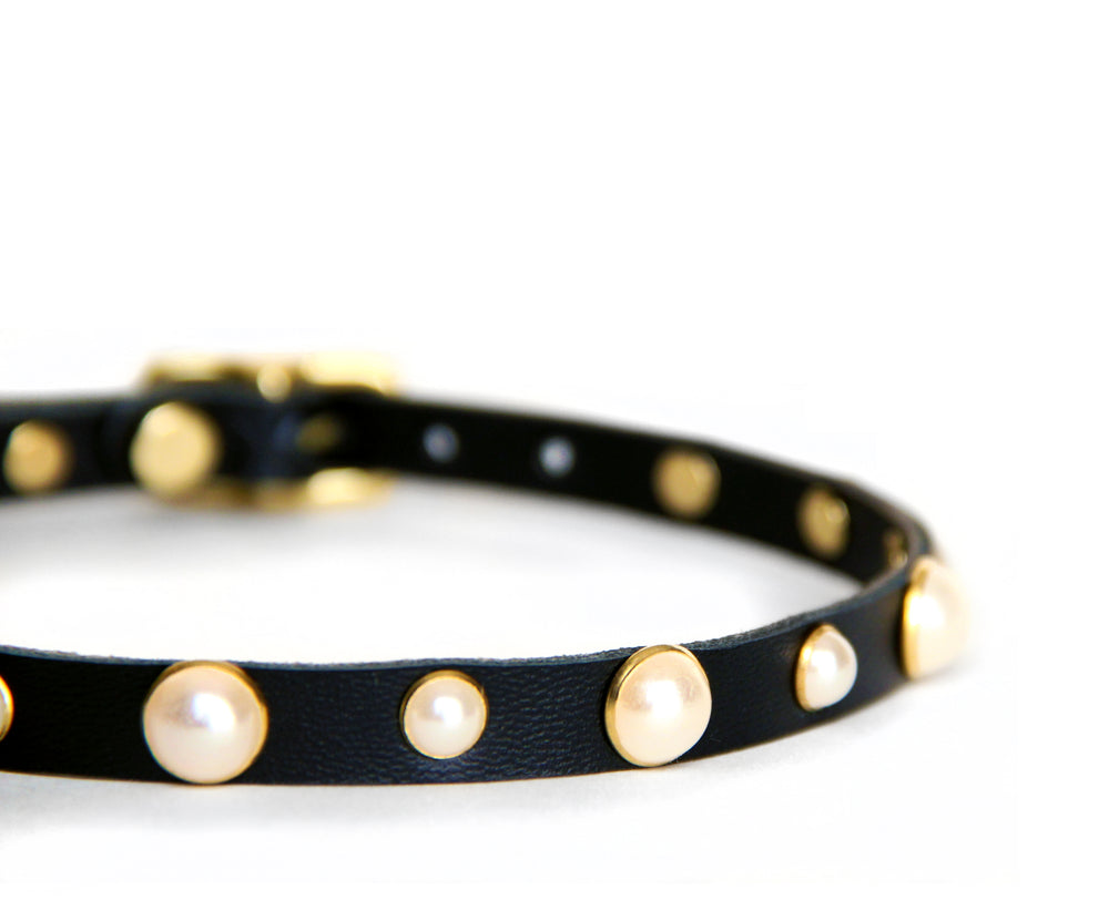 Closeup of black choker shows the alternating sizes of pearl studs: large, small, large, small.....