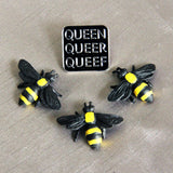 A trio of plastic toy bees stand before a Q-words pin on a silver-toned fabric background.