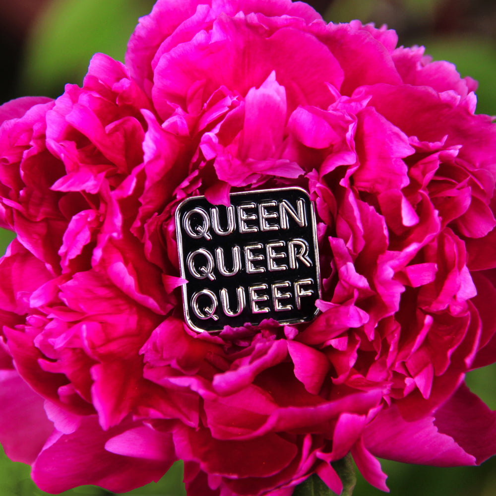 A bright magenta peony in full bloom holds a Q-words pin. The pin is nestled in the center of the flower's petals.