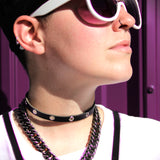 Model faces the sunshine in sunglasses, a thin black leather choker with silver grommets, a chain and a chest harness.