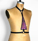 Black leather harness with upside down purple mermaid leather triangle in the center, angled front view
