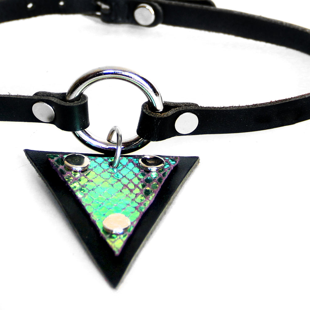 Close up of Trianthem O-ring choker on white background. At this angle, iridescent scales on pendant are shining teal.