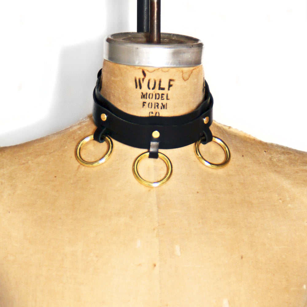 Dressform adorned with a black leather choker with three bright brass o-rings at the front.