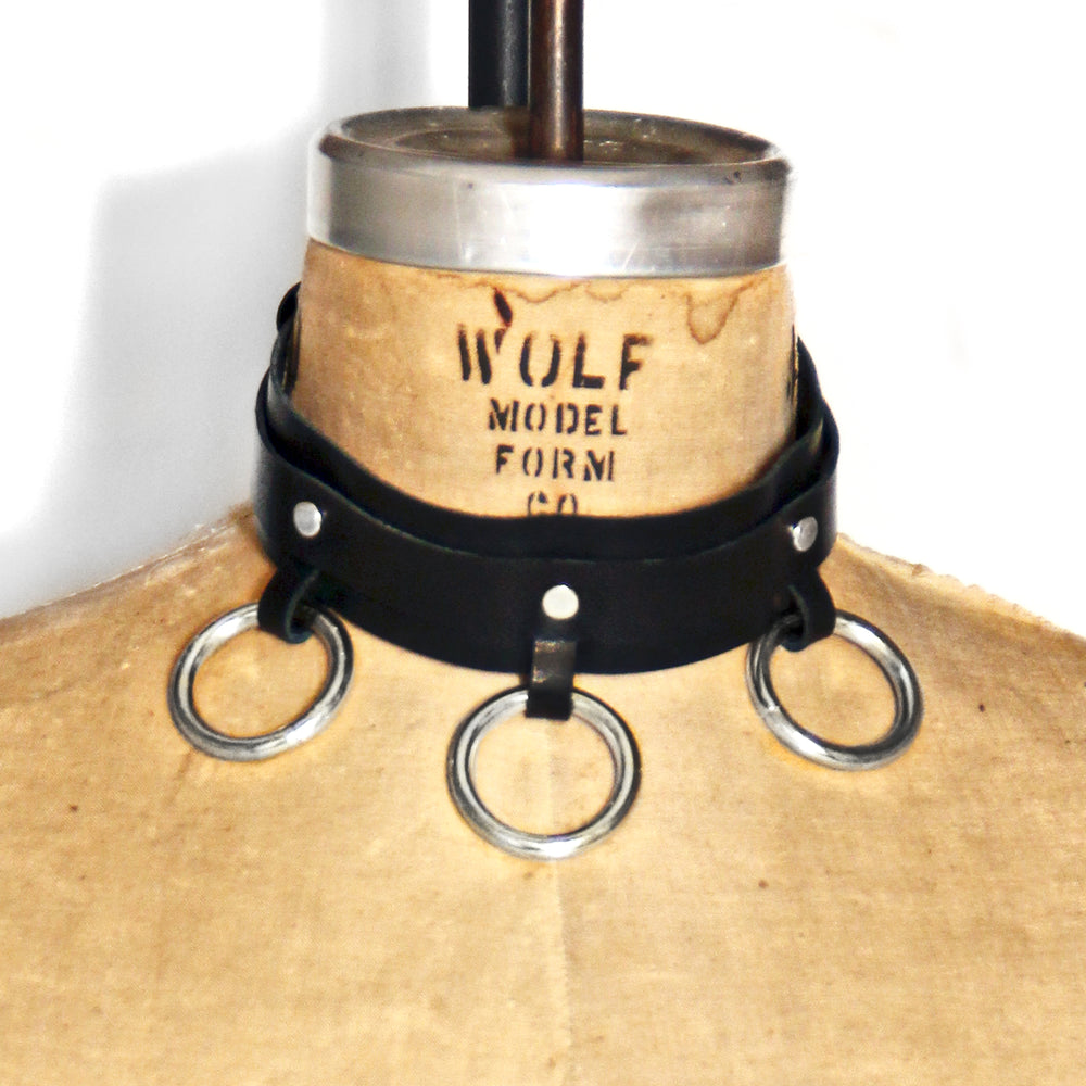 Dressform adorned with a black leather choker with three silver o-rings at the front.
