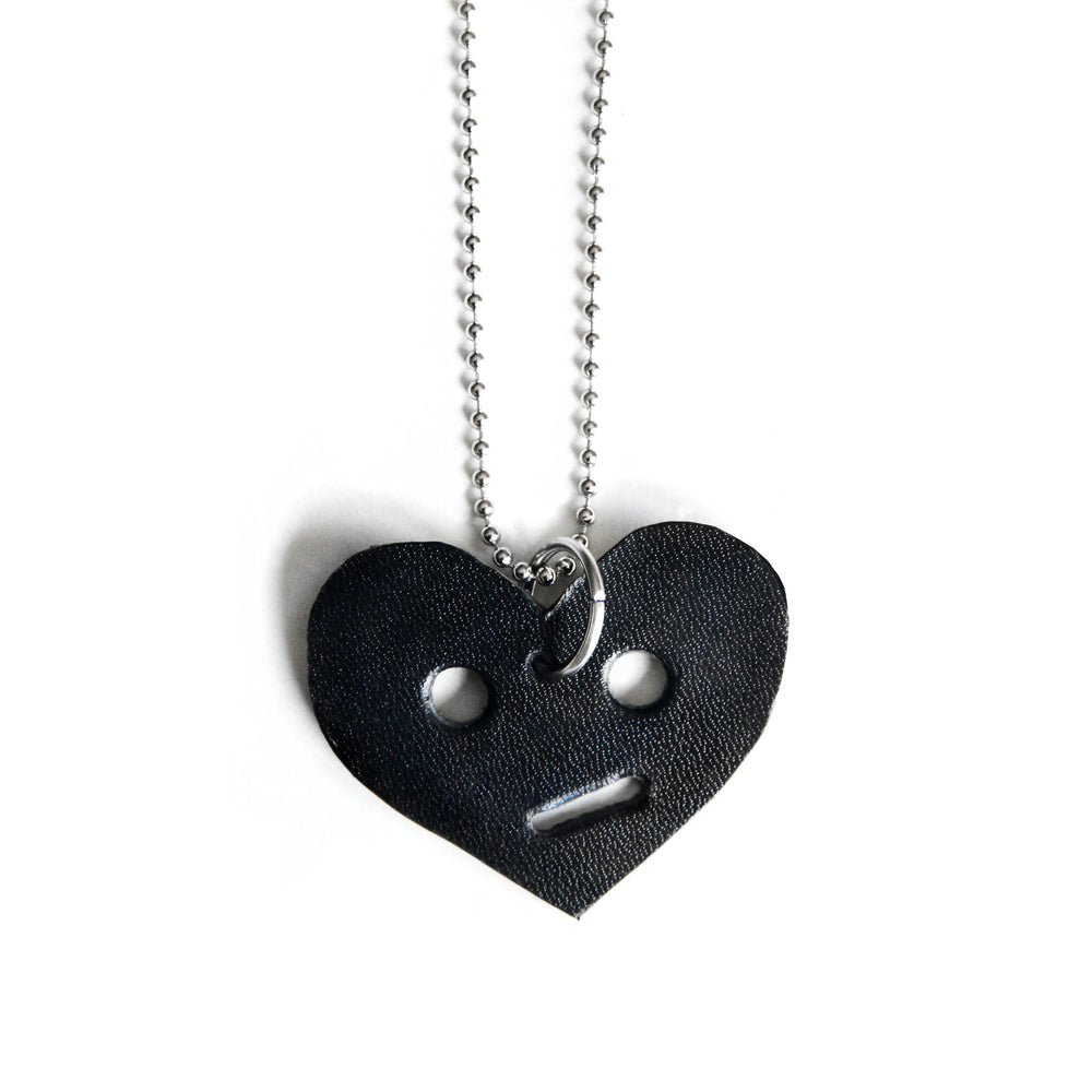Leather heart necklace with circle eyes, close up