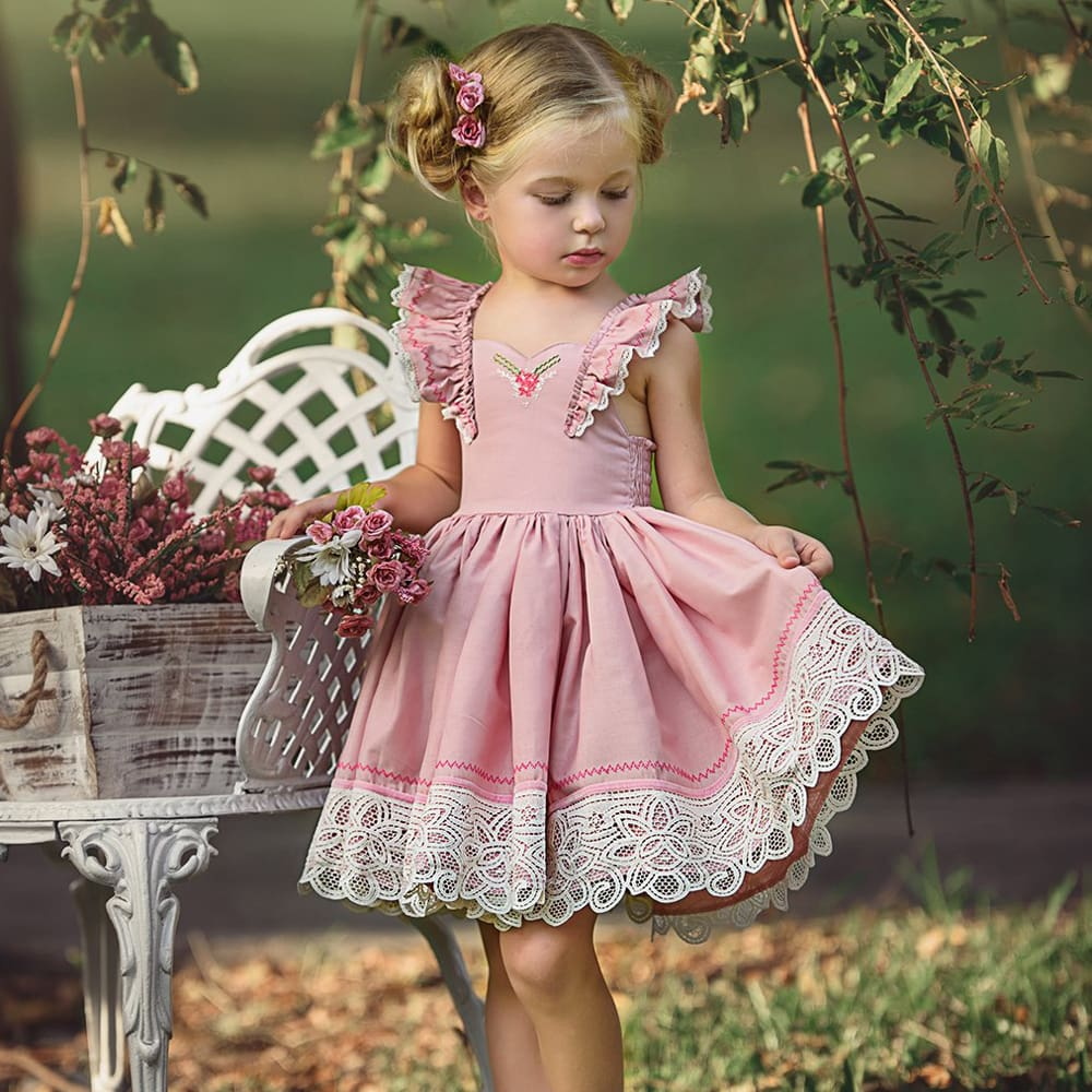 a little girl in a pink dress standing in front of a flower