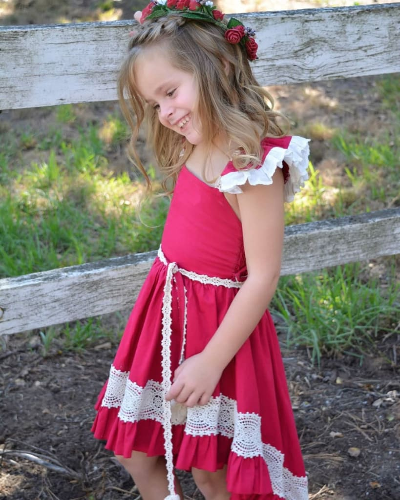 a little girl in a red dress sitting on a bench