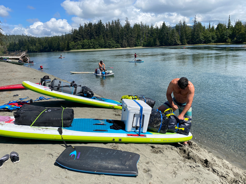 packing up paddle sboars on the beach for next day's adventure
