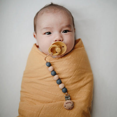 baby in mushie organic cotton muslin swaddle blanket yellow