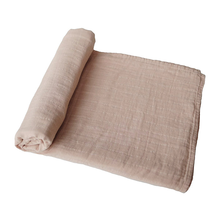 mushie organic cotton muslin swaddle blanket for baby in pale taupe