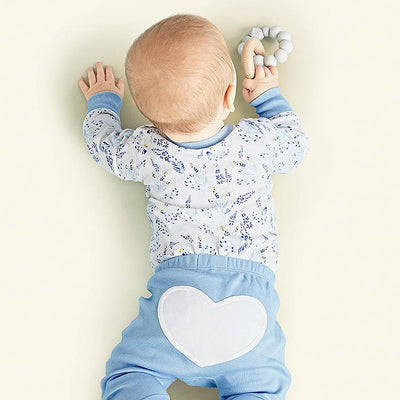 baby wearing meadow blue organic cotton bodysuit and heart pants