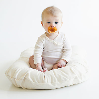 baby sitting on organic cotton bed lounger