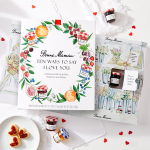 "Open box of Bonne Maman® ""Ten Ways to say I Love you"" gift with 10 mini jars of preserves and honey. Table decorated with Valentine's day cookies and hearts."