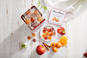Bonne Maman® Pates de Fruits with an open Pates de Fruit container, apples, cinnamon sticks, oranges, and strawberries on a white table