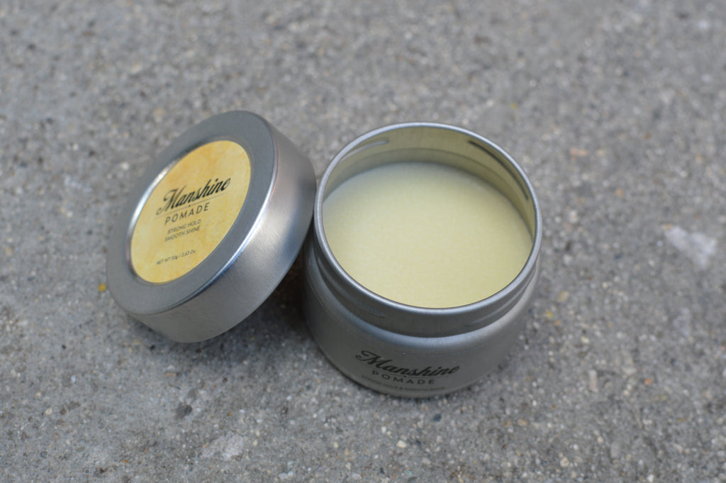 Open can of manshine showing its cream colored pomade