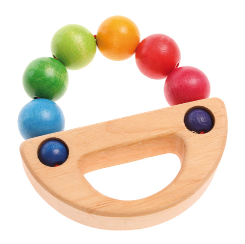 A wooden baby toy with rainbow balls in an arc that meets a natural wooden handle to create a circle on a white background.