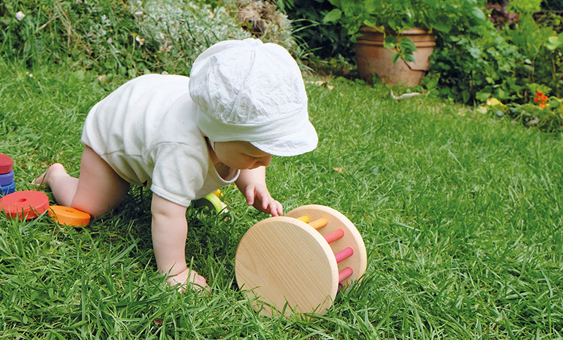 an outdoor scene with a baby in a white bonnet on a grassy hill crawling after the rolling wheel.