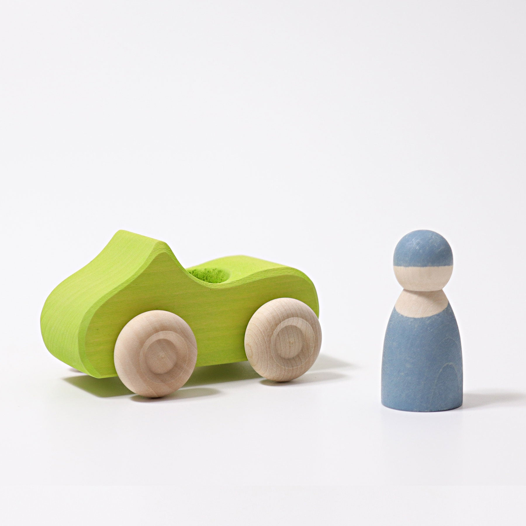 Small Green wooden Convertible Car next to a blue wooden peg doll on a white background.
