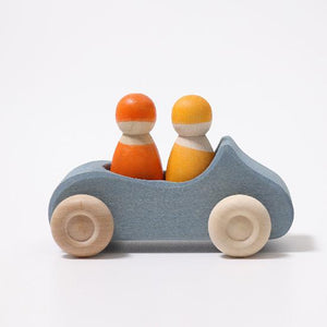 on a white background, a blue wooden convertible car with two peg dolls inside, one yellow, one orange