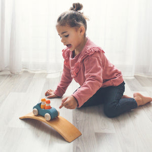 a girl playing in an interior space in front of a white curtain on a wood floor. She's playing with a blue wooden convertible car with two peg dolls inside, one yellow, one orange on a curved wooden bridge.
