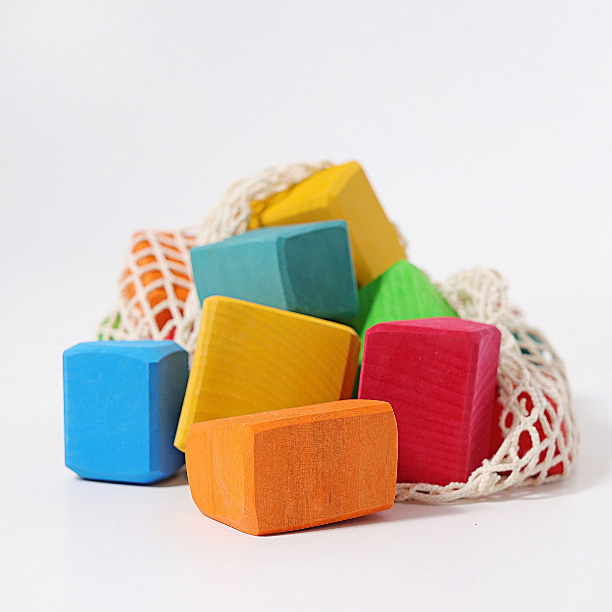 a bag of colourful wooden blocks in a net bag in a white setting.