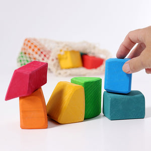 a hand stacking a blue wooden block onto other colourful blocks in the foreground. The rest of the blocks are in a net in the background. In a white setting.