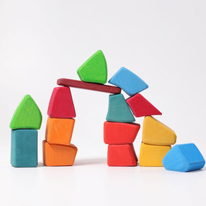 a stack of organically shaped colourful wooden blocks in a white setting