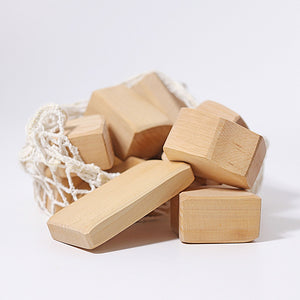 a bag of natural wooden blocks in a net bag in a white setting.