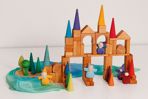 in a white room, wooden building blocks coupled with rainbow coloured cones arranged in a structure with a blue piece of silk arranged at the bottom. Plush gnomes are included in the structure.