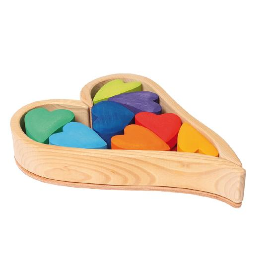 rainbow coloured hearts stored in a natural heart-shaped wooden frame on a white background