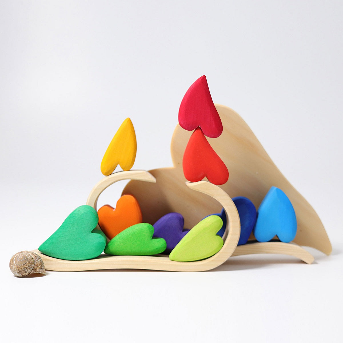 on a white background, natural wooden curved pieces with colourful wooden hearts balanced on them. A snail shell in the foreground.