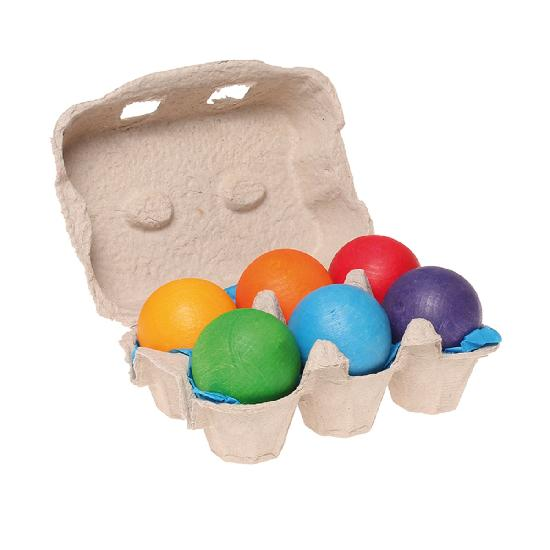 On a white background,  half an egg carton open to reveal six different coloured rainbow balls inside