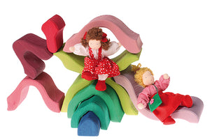 Pieces of a wooden Lotus flower stacker in red, pink, purples, greens and blue with dolls using pieces as beds and slides on a white background