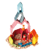 on a white background, wooden sturctures in various colours in a pile of sand with wooden peg dolls and glittery gems