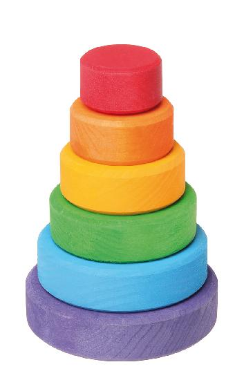 On a white background, a small wooden stacking tower with rings in rainbow colours