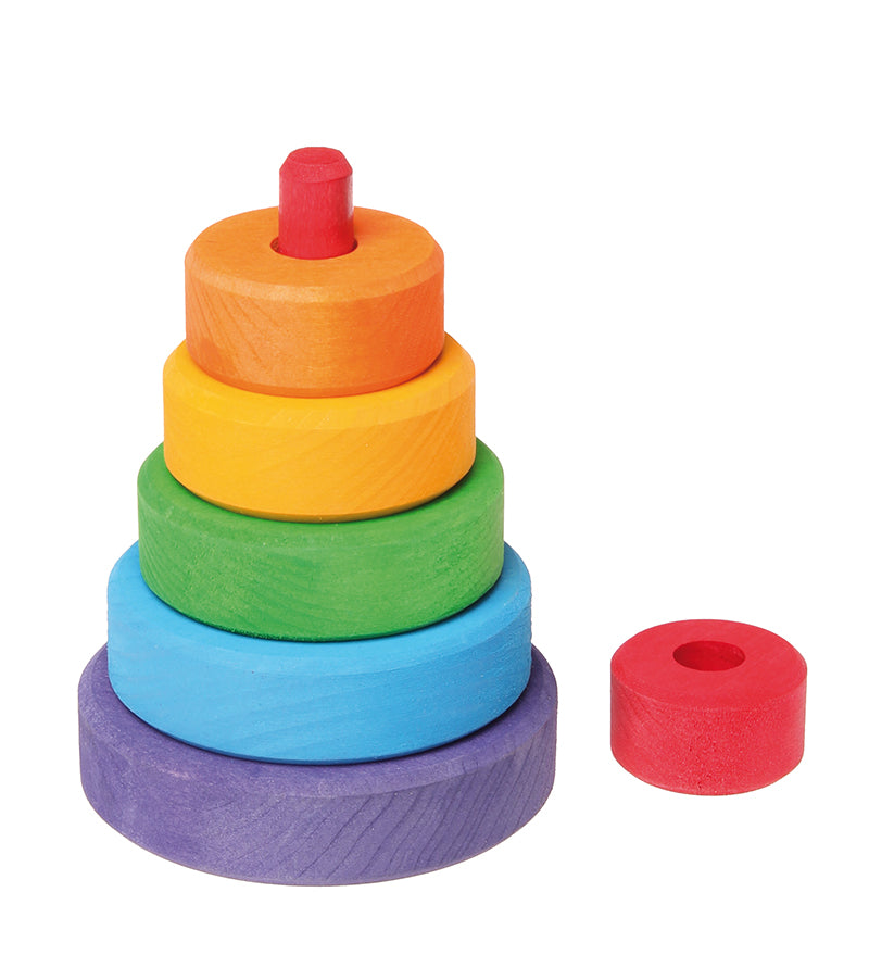 On a white background, a small wooden stacking tower with rings in rainbow colours. The top red piece is removed to reveal a red stick that the rings are stacked upon.