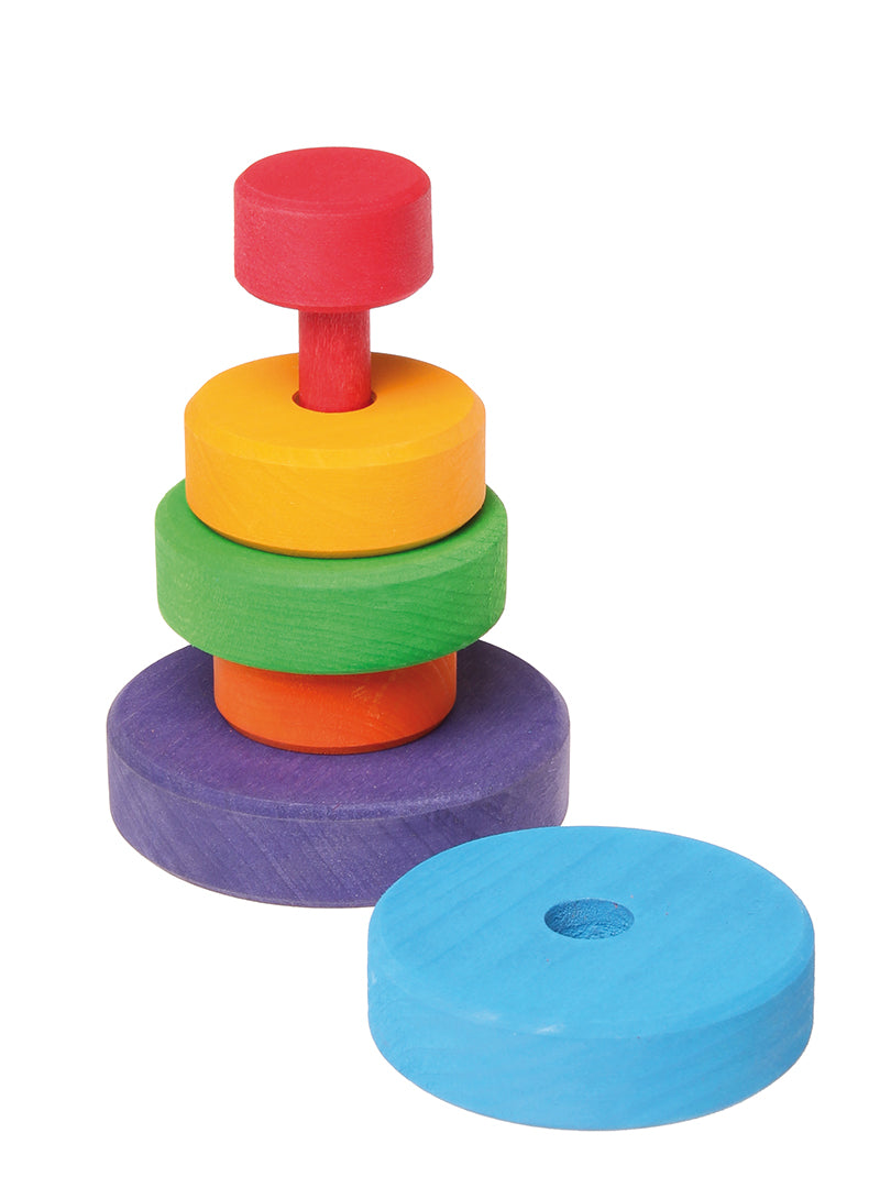 On a white background, a small wooden stacking tower with rings in rainbow colours. The rings are stacked outside of size and colour order in a creative fashion. One blue ring rests next to the tower