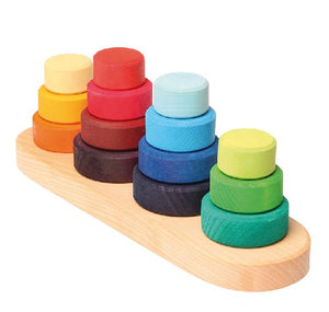 on a white background, four stacks of multi coloured discs on a natural wooden base.