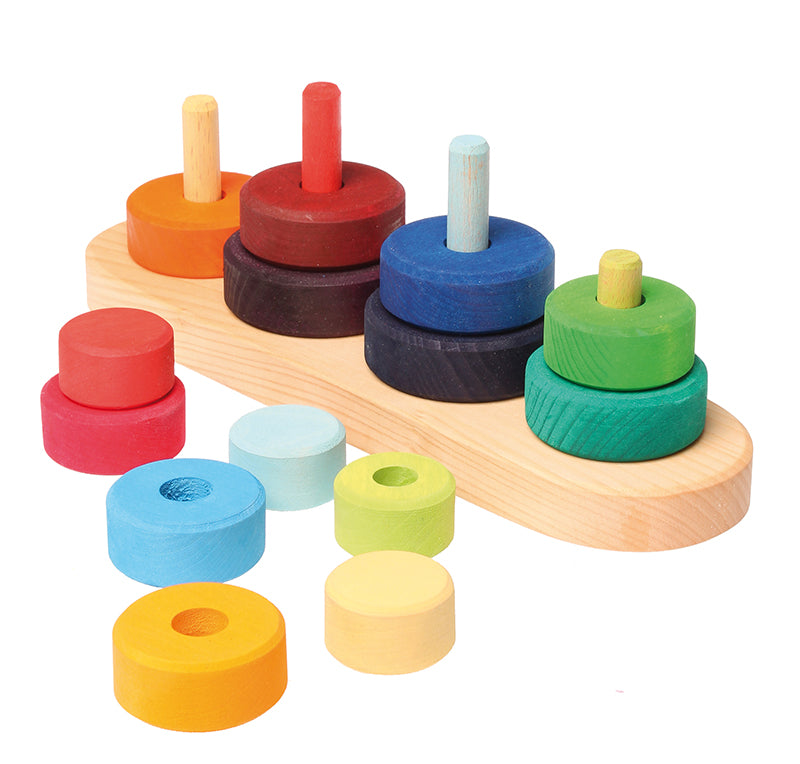 on a white background, four stacks of multi coloured discs on a natural wooden base. Some discs are removed to reveal posts that each stack of discs sits on.