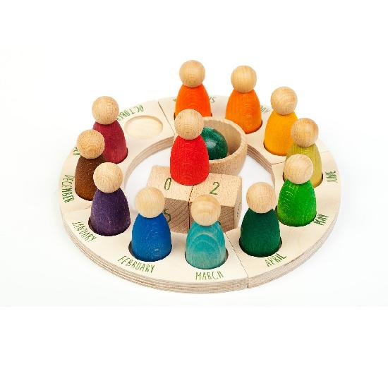 on a white background, a wooden perpetual ring calendar with a different coloured peg doll for each month of the year
