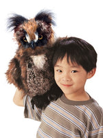 a boy with black hair holding a great horned owl puppt on his shoulder on a white background