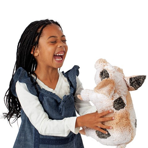 a girls with braids laughing and holding holding a a plush pink pig with grey spots on a white background